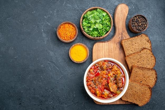 Vista dall'alto deliziosa zuppa con verdure e pane scuro su spazio grigio