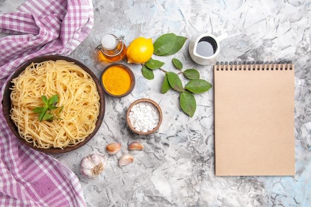 上面図白いテーブルパスタミール生地ディシャのプレート内のおいしいスパゲッティ