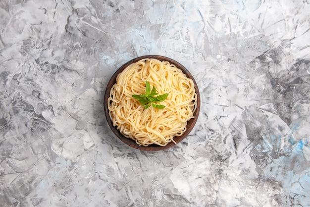 上面図白いテーブル皿パスタミール生地に緑の葉とおいしいスパゲッティ
