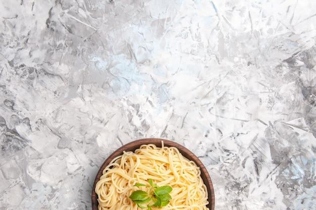 Vista dall'alto deliziosi spaghetti con foglia verde su pasta bianca per piatti da tavola