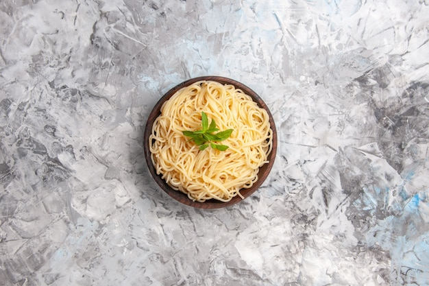 Vista dall'alto deliziosi spaghetti con foglia verde sul piatto da tavola bianco pasta pasto