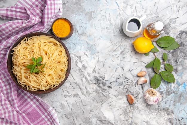 ライトホワイトのテーブルパスタミール生地に調味料を加えたトップビューの美味しいスパゲッティ