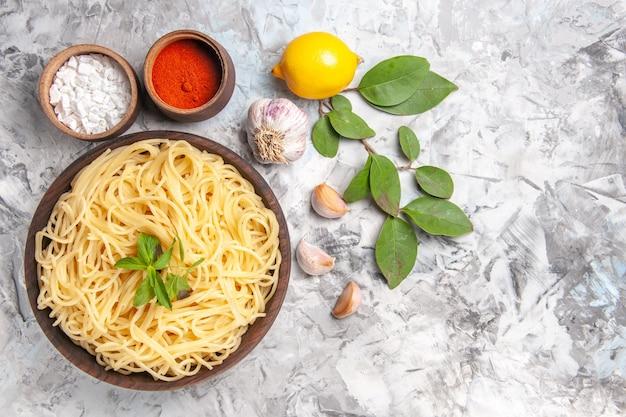上面図白いテーブルディナーパスタ生地の食事に調味料とおいしいスパゲッティ