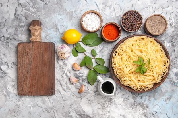 白いテーブルディナーパスタ生地に調味料を使ったトップビューのおいしいスパゲッティ