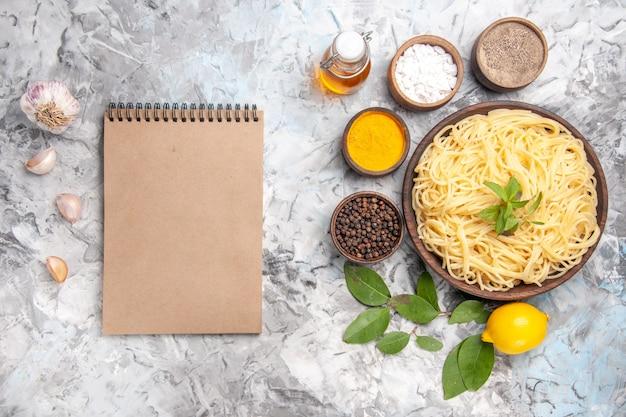 白いテーブルの食事料理のパスタに調味料を入れたトップビューのおいしいスパゲッティ