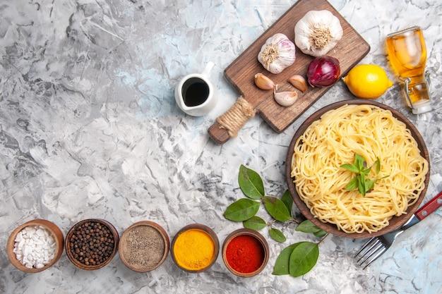 白いテーブルミールパスタ生地の色に調味料を使ったトップビューのおいしいスパゲッティ