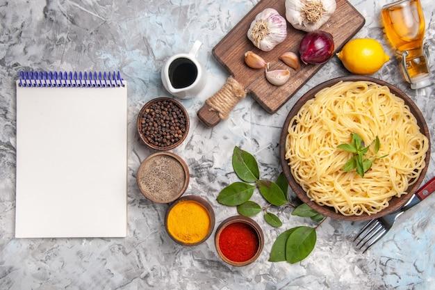 白いテーブルミールパスタ生地に調味料を使ったトップビューのおいしいスパゲッティ