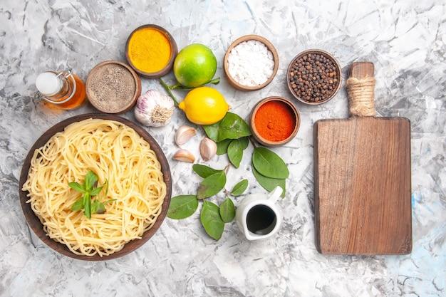 上面図白いテーブルパスタ生地の食事に調味料とおいしいスパゲッティ
