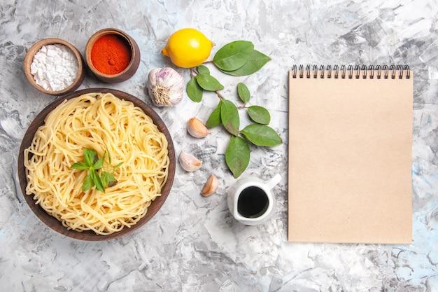Vista dall'alto deliziosi spaghetti con condimenti su pasta di pasta per cena sul pavimento bianco