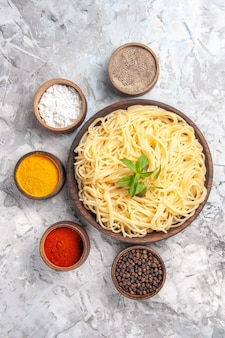 Top view delicious spaghetti with seasonings on white table meal dough dish pasta
