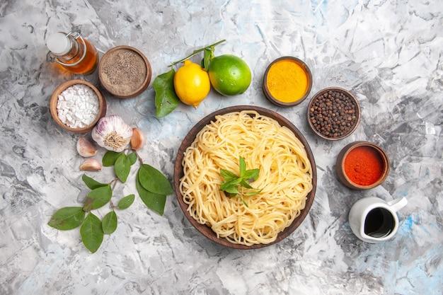 Vista dall'alto deliziosi spaghetti con condimenti su pasta bianca da tavola