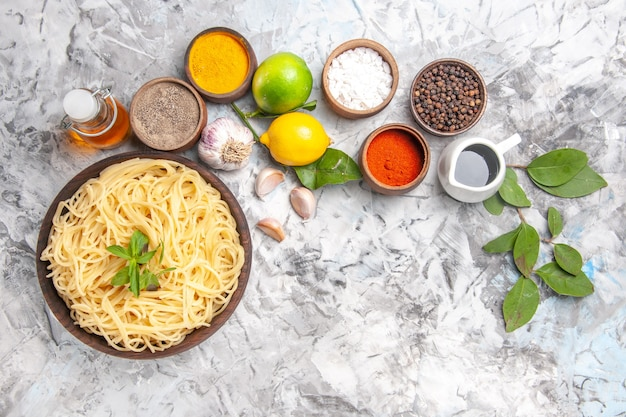Top view delicious spaghetti with seasonings on white table meal pasta dough