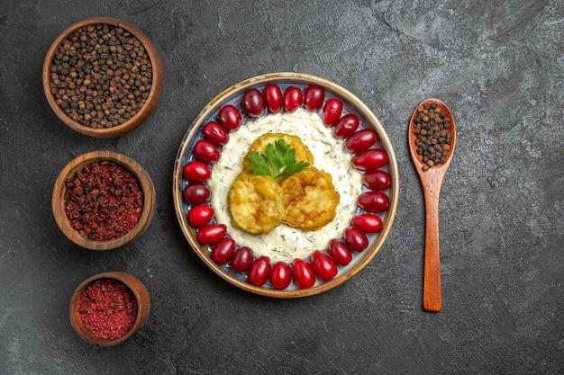 Vista dall'alto di un delizioso pasto di zucca con cornioli rossi freschi e condimenti su una superficie grigia