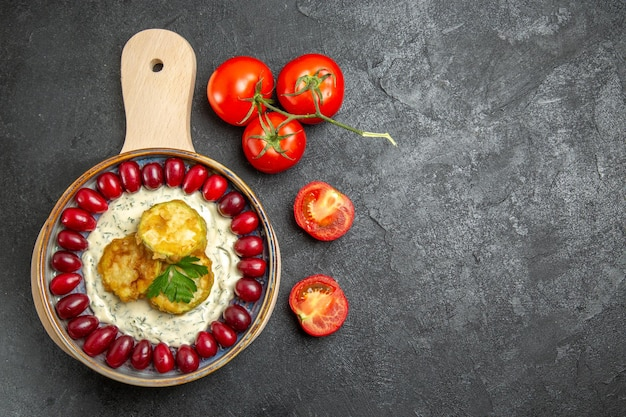 Vista dall'alto del delizioso pasto di zucca con cornioli rossi freschi e pomodori sulla superficie grigia