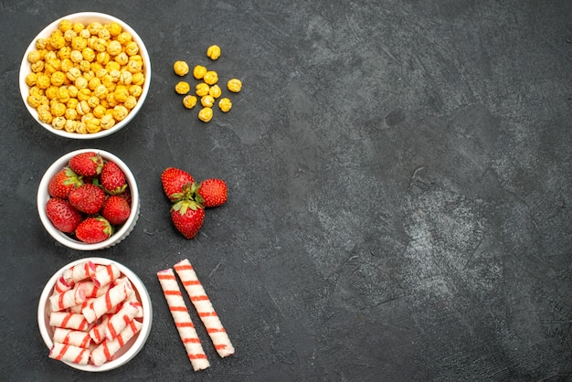 Вид сверху вкусной клубники со сладостями на черном фоне со свободным пространством