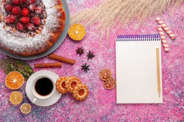 トップビューライトピンクの背景ケーキに砂糖粉とお茶で焼いたおいしいストロベリーケーキ甘い砂糖ビスケットクッキーパイ