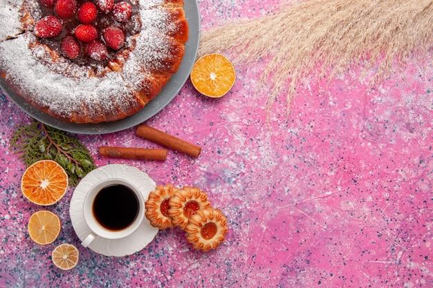 トップビューライトピンクの背景ケーキに砂糖粉クッキーとお茶で焼いたおいしいストロベリーケーキ甘い砂糖ビスケットクッキーパイ