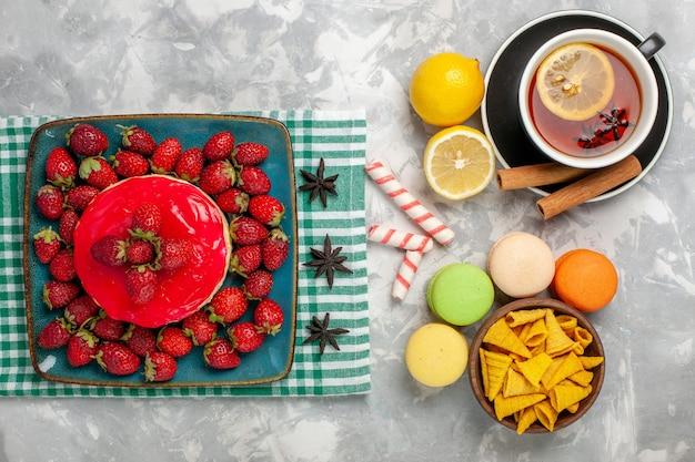 Вид сверху вкусный клубничный торт со свежей клубникой и чашкой чая на белой поверхности торт бисквитное ягодное сахарное сладкое печенье