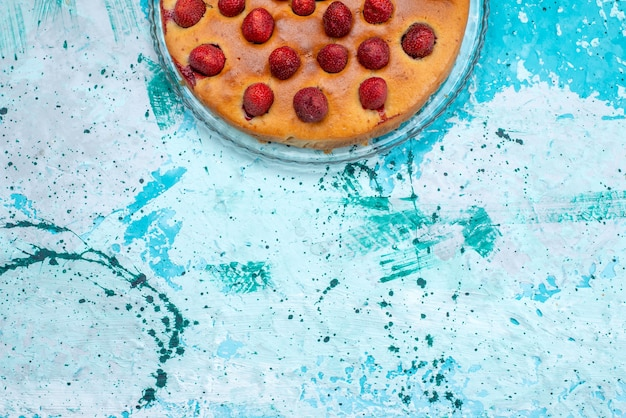 Top view of delicious strawberry cake round shaped with fruits on top on bright-blue, cake dough sweet biscuit fruit berry