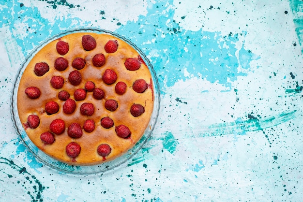 Top view of delicious strawberry cake round shaped with fruits on top on bright-blue, cake dough sweet biscuit sugar fruit berry