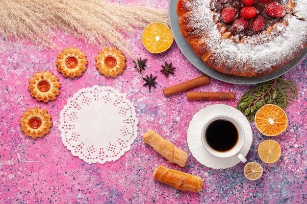 Вид сверху вкусный клубничный торт сахарной пудры торт с печеньем и чашкой чая на розовом фоне торт сладкий сахарный бисквитный пирог с печеньем