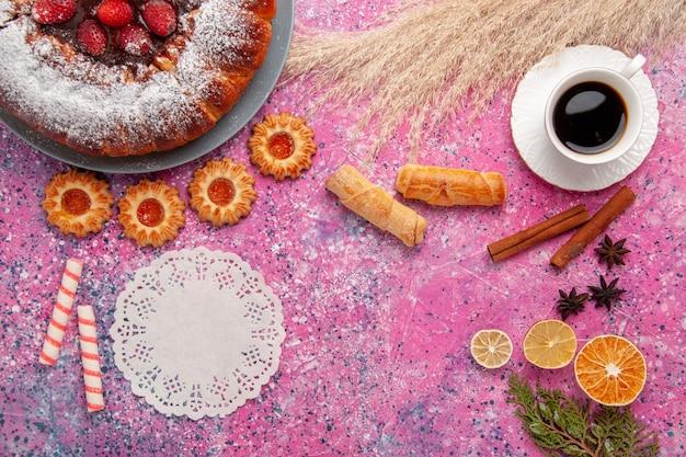 上面図おいしいストロベリーケーキシュガーパウダーケーキとクッキーベーグルとピンクの背景にお茶のカップ甘い砂糖クッキーパイ
