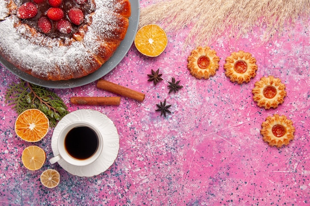 Vista dall'alto deliziosa torta di fragole torta di zucchero in polvere con biscotti e tazza di tè su sfondo rosa torta di biscotti dolci di zucchero torta