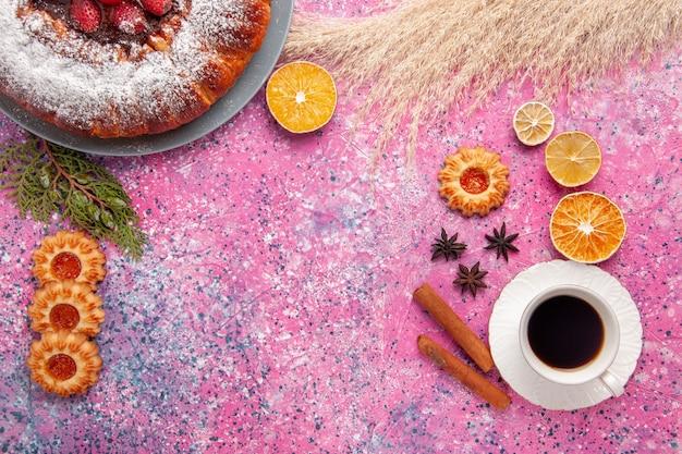 Vista dall'alto deliziosa torta di fragole torta di zucchero in polvere con i biscotti e la tazza di tè su sfondo rosa torta dolce torta di biscotti di zucchero