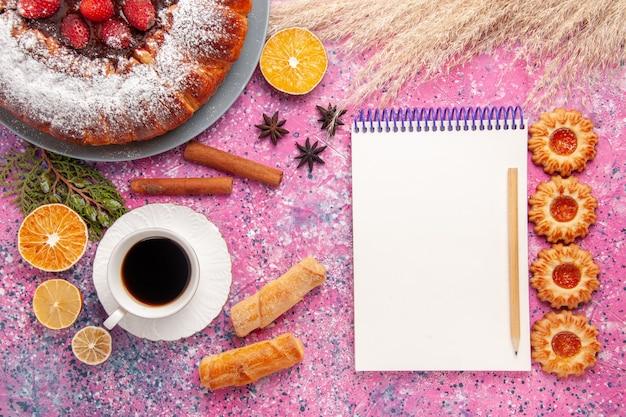 Vista dall'alto deliziosa torta di fragole torta di zucchero a velo con i biscotti e la tazza di tè sulla torta da scrivania rosa dolce zucchero biscotto torta biscotti