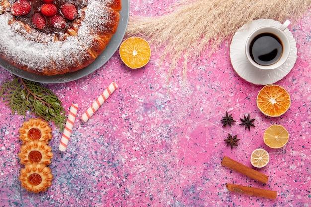 Vista dall'alto deliziosa torta di fragole torta di zucchero a velo con piccoli biscotti e tazza di tè sulla torta rosa scrivania torta di biscotti di zucchero dolce