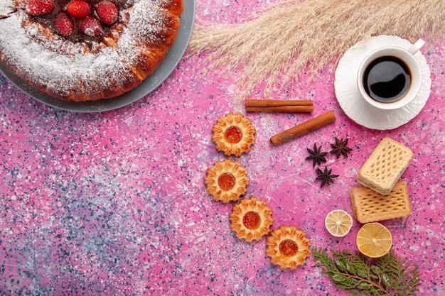Vista dall'alto deliziosa torta di fragole torta di zucchero in polvere con cialde piccoli biscotti e tazza di tè sulla torta rosa scrivania torta di biscotti di zucchero dolce