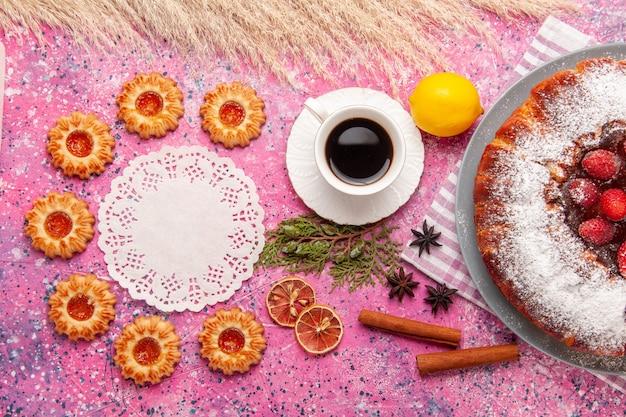 Вид сверху вкусный клубничный торт сахарная пудра с печеньем лимон и чай на розовом фоне торт сладкое сахарное печенье печенье чай