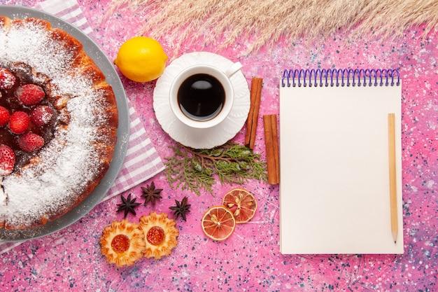 Вид сверху вкусный клубничный торт сахарная пудра с печеньем блокнот и чай на розовом фоне торт сладкое сахарное печенье печенье чай