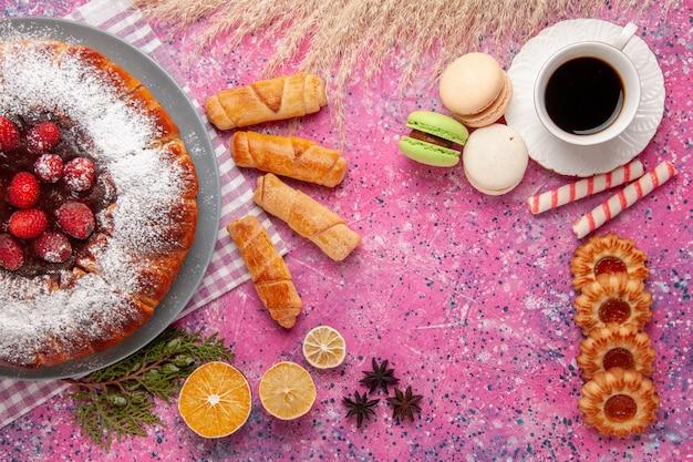 Vista dall'alto deliziosa torta alla fragola con zucchero a velo con una tazza di tè macarons francesi e bagel sulla torta da scrivania rosa biscotti dolci biscotti allo zucchero