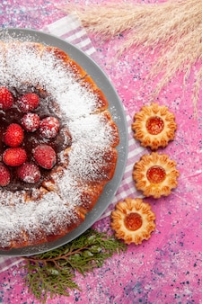 Вид сверху вкусный клубничный торт с сахарной пудрой с маленьким печеньем на розовом фоне торт сладкое печенье печенье чай