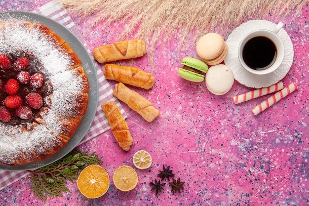 Вид сверху вкусный клубничный торт сахарная пудра с чаем макароны на розовом фоне торт сладкое печенье печенье чай