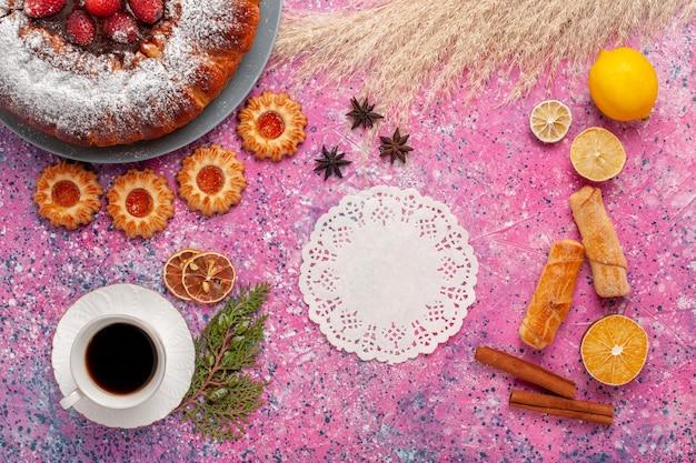 ベーグルクッキーとピンクの背景のケーキの甘い砂糖クッキーパイにお茶のトップビューおいしいストロベリーケーキ