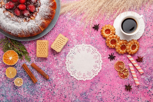 トップビューライトピンクの背景にクッキーとお茶のおいしいストロベリーケーキを焼く甘い砂糖ビスケットクッキーパイ