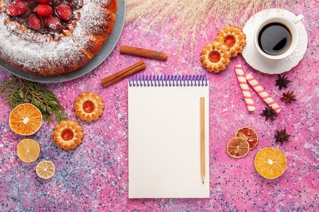 上面図ピンクの背景にクッキーとお茶のおいしいストロベリーケーキを焼く甘い砂糖ビスケットクッキーパイ