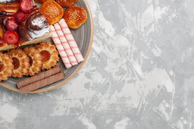 トップビュークッキーとライトホワイトの背景に小さなケーキとおいしいストロベリーケーキビスケットシュガーケーキ甘いパイクッキー