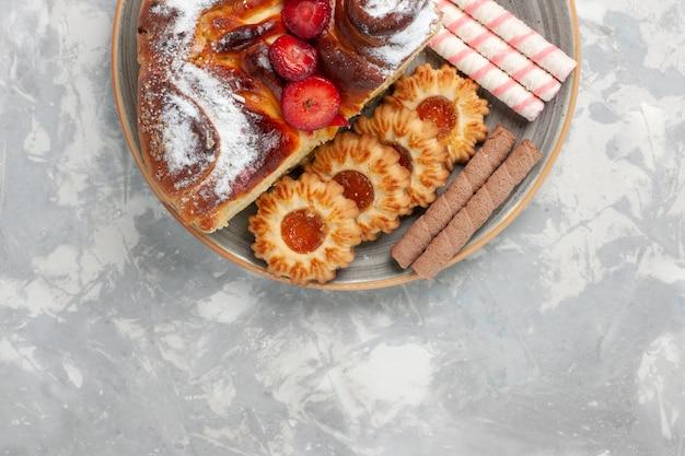 トップビュークッキーとライトホワイトの表面に小さなケーキが付いたおいしいストロベリーケーキビスケットシュガーケーキスイートパイクッキー