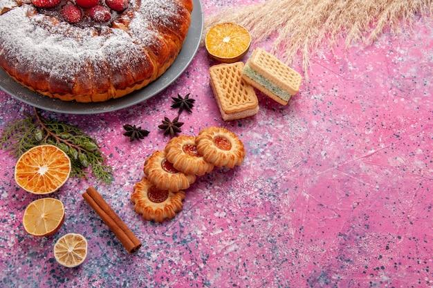 上面図ピンクの背景にクッキーとワッフルが付いたおいしいストロベリーケーキケーキは甘い砂糖ビスケットクッキーパイを焼く