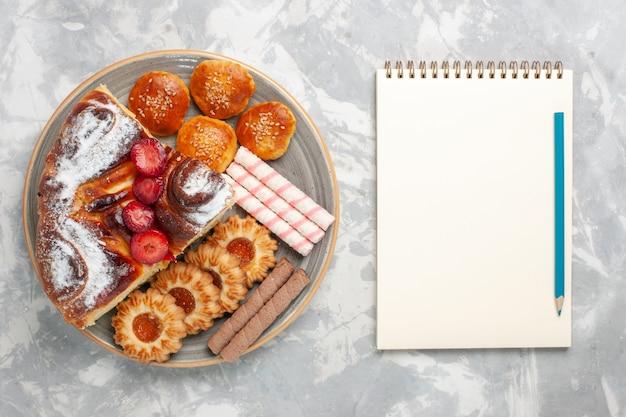 Vista dall'alto deliziosa torta di fragole con biscotti e piccole torte sul biscotto bianco scrivania torta di zucchero torta dolce biscotto