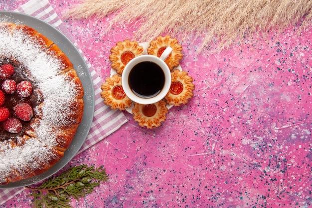 上面図ピンクの背景ケーキ甘いビスケットシュガークッキーにお茶とクッキーのカップとおいしいストロベリーケーキ