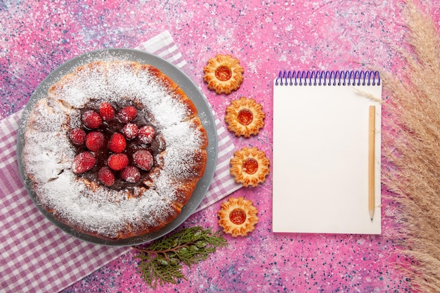 上面図メモ帳と淡いピンクの表面においしいストロベリーケーキ