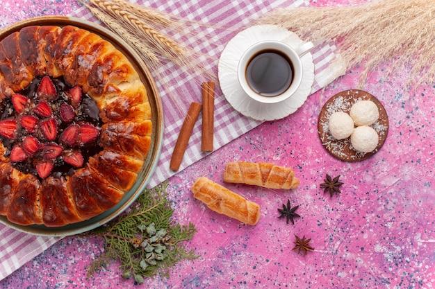 Vista dall'alto deliziosa torta fruttata torta di fragole con una tazza di tè su rosa chiaro