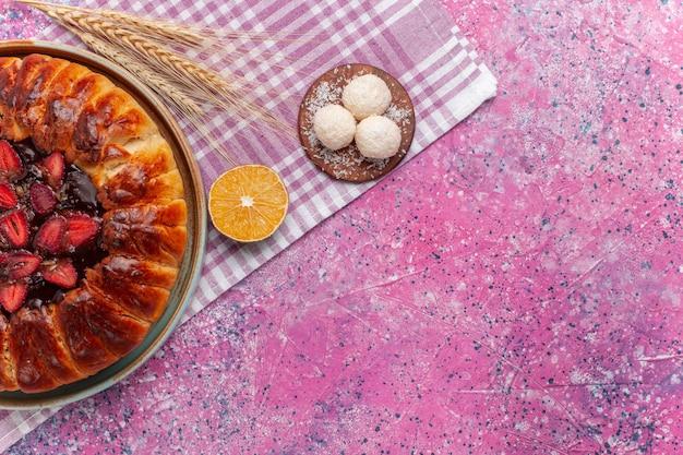 Vista dall'alto una deliziosa torta di fragole tonda formata torta fruttata sul rosa