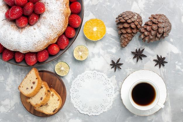 Vista dall'alto deliziosa torta di fragole con una tazza di tè su bianco