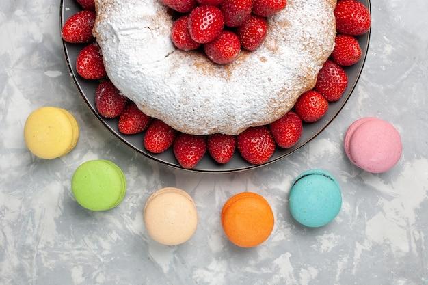 Vista dall'alto deliziosa torta di fragole con macarons francesi su bianco
