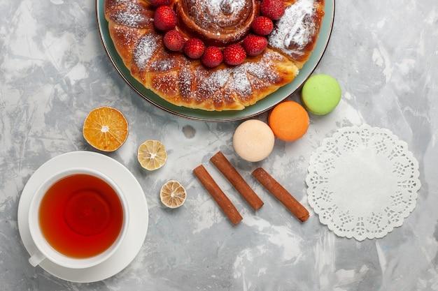 흰색 표면 비스킷 설탕 케이크 달콤한 빵 파이에 마카롱과 차 한잔 상위 뷰 맛있는 딸기 파이